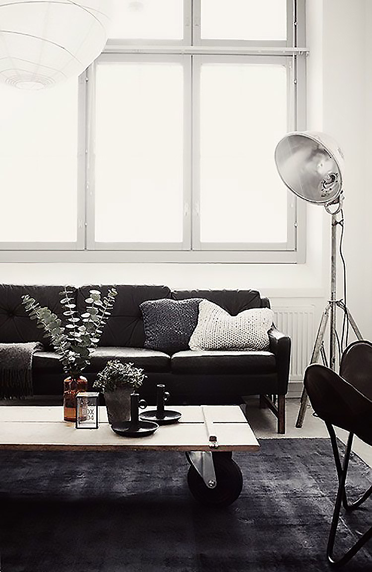 Industrial chic living room with black sofa and rug