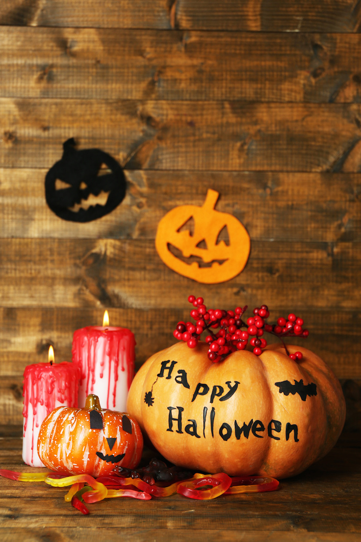 Halloween pumpkins and candles on wooden table background
